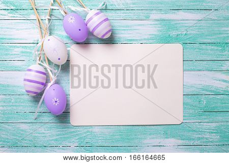 Easter or spring background. Decorative violet eggs and empty tag on turquoise wooden background. Selective focus. Place for text.