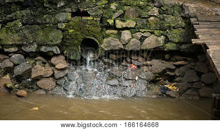 a water pipeline ended up at dirty canal photo taken in Jakarta Indonesia java