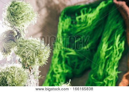 Details of green yarn skeins and clews. Eco style yarn shop background. Selective focus