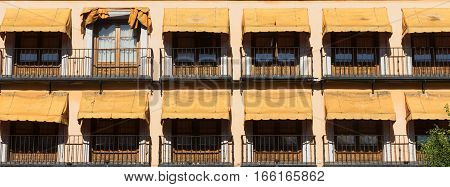 Toledo (Castilla-La Mancha Spain): facade of historic building with balconies and yellow curtains in the Zocodover square