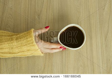Woman's hand with red manicure is going to take cup of coffee