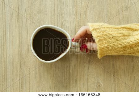 Woman's hande with red manicure is going to take cup of coffee