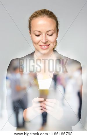 Beautiful young caucasian businesswoman in business attire using smart phone application. Double exposure with abstract blur of business people overlay.