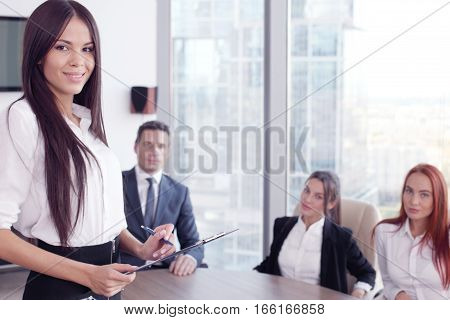 Group portrait of a professional business woman and team looking confidently at camera
