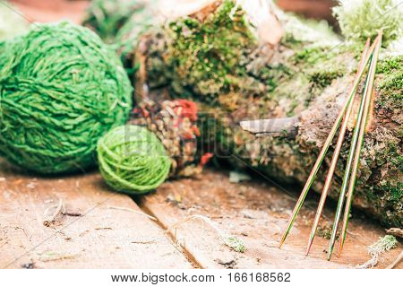 Colorful wood sock needles and green yarn balls near raw log. Concept of environmental friendly yarn shop
