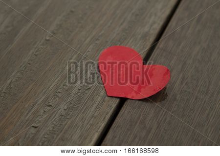 Red wet paper heart on wood background love concept