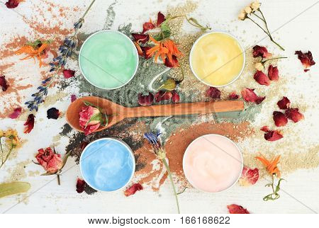 Sampler set preparation of different clay facial masks in jars, powder and dried herbs scattered, top view skincare ingredients.