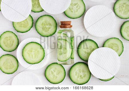 Fresh homemade vegan facial toner in bottle, green cucumber slices, cotton-pads, top view ingredients.
