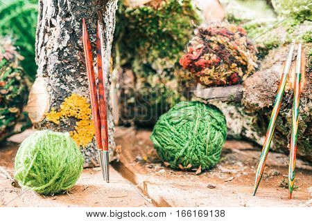 Variety of green yarns and wooden needles with raw wood decorations. Concept of environmental friendly yarn shop. Close up