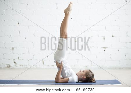 Girl child practicing yoga, standing in salamba sarvangasana exercise, supported Shoulder stand pose, working out wearing sportswear, t-shirt, pants, indoor full length, white loft studio background