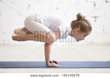 Side view of Girl child practicing yoga, standing in Crane exercise, Bakasana pose, working out wearing sportswear, t-shirt, pants, indoor full length, white loft studio background