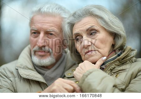 Close-up portrait of thoughtful senior couple outdoors