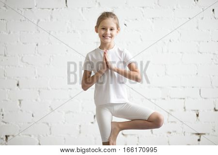 Portrait of smiling happy girl child practicing yoga, standing in Vrksasana exercise, Tree pose with Namaste, working out wearing sportswear, t-shirt, pants, indoor, white studio background