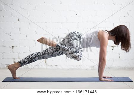 Young attractive woman practicing yoga, doing Push ups, press ups, phalankasana exercise, Plank pose variation, working out wearing sportswear, pants and top, indoor full length, white loft background