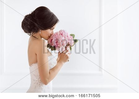 Beautiful bride perfect style. Wedding hairstyle make-up luxury wedding dress and bride's bouquet. Young attractive multi-racial Asian Caucasian model like a bride against white room smells at bouquet. Side view