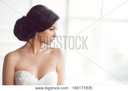 Beauty portrait of bride wearing fashion wedding dress with feathers with luxury delight make-up and hairstyle, studio indoor photo. Young attractive multi-racial Asian Caucasian model. Profile of sensual beautiful young woman like a bride in white room a