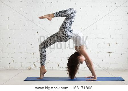 Young attractive woman practicing yoga, standing in Bridge exercise, One legged Wheel pose, working out wearing sportswear, pants and top, indoor full length, white loft studio background, horizontal