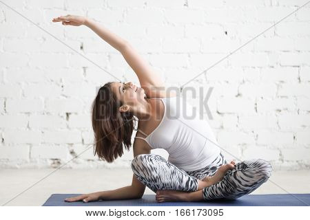 Young cheerful attractive woman practicing yoga, sitting in Sukhasana pose, side bend exercise, working out wearing sportswear, top, pants, indoor full length, white loft studio background