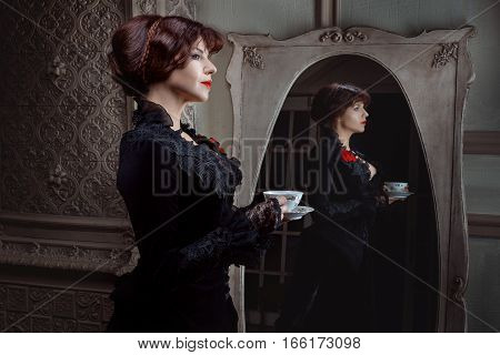 Woman in old-fashioned style with a cup in his hands.