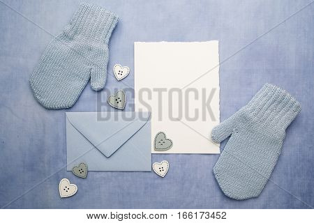 Small baby gloves, blank card and evelop on blue fabric background.