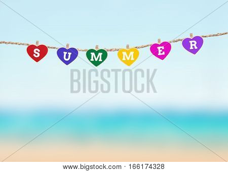 wooden clipboard heart shape with summer wording hang on clothesline over blury summer beach background