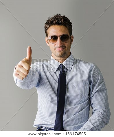 A different kind of young business man wearing shirt, tie doing OK sign with thumb up, on light background