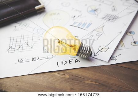 paper with light bulb and pen table