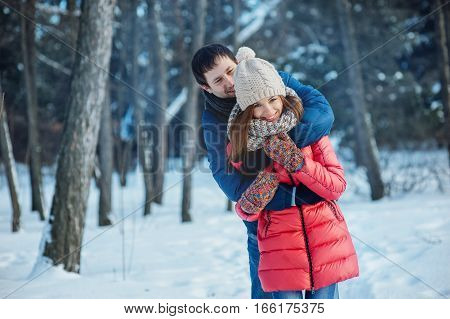 Guy and girl walk , have fun in the forest in winter