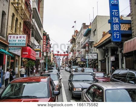 San Francisco, USA - May 25, 2007: Chinatown street with cars and decorations during daytime