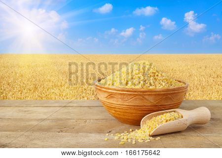Bulgur or couscous in bowl. Bulgur in ceramic bowl on table with field of wheat on the background. Agriculture and harvest concept. Ripe wheat field, blue sky, sun