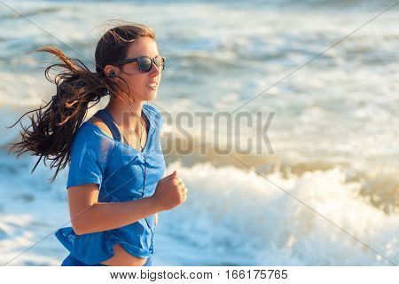 Running woman. Female runner jogging during outdoor workout on beach listening to music in earphones. Fitness woman running by the beach at sunrise. Healthy active lifestyle girl exercising outdoors
