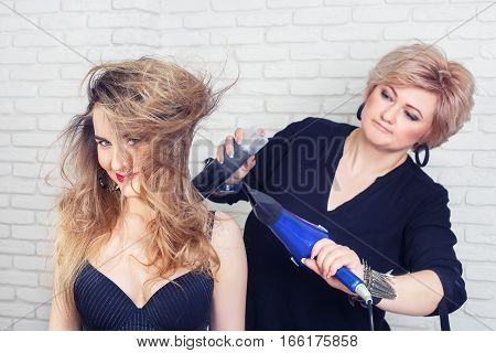 hairdresser blow drying woman's hair after giving a new haircut. Portrait of happy woman at the hair salon. Hairdresser making hot styling with use hair dryer and spray