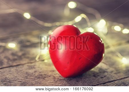 garland lights and red heart on wooden background. Love, valentine's day concept. Valentine's day background with heart. Photo with toning