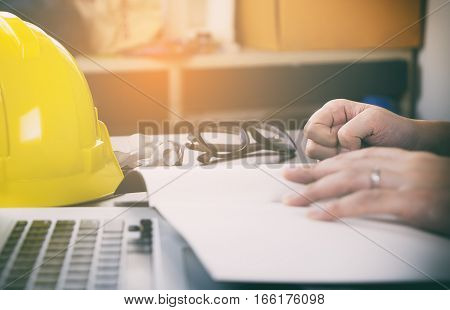 Engineer construction is having trouble with his project. His fist hitting the table.