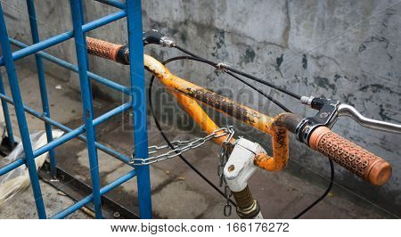Orange handlebar of a parked bicycle locked by a chain photo taken in jakarta indonesia java