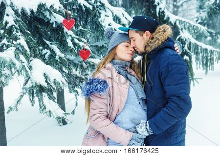 Young pregnant couple in winter forest. Expectant mother and her husband waiting for baby in winter. Love, family, pregnancy concept. Future parents walking and hugging outdoors. Happy family