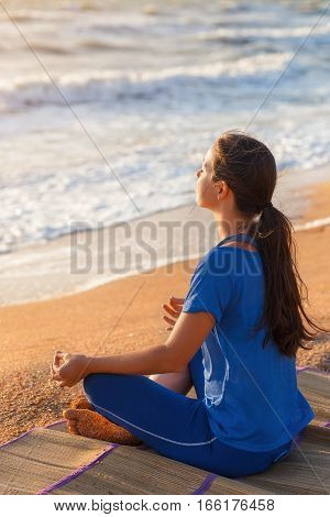 yoga in the sea or ocean beach. Girl meditating in lotus pose at sunrise. Healthy lifestyle. Morning meditation.Yoga meditation concept. Young woman practicing yoga outdoors