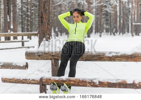 Fit woman doing sit ups working out on abdominal muscles exercising to improve core muscle strength cross training outdoors winter park