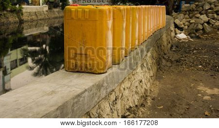 Jerry cans stands in a row near dirty river photo taken in Jakarta Indonesia java