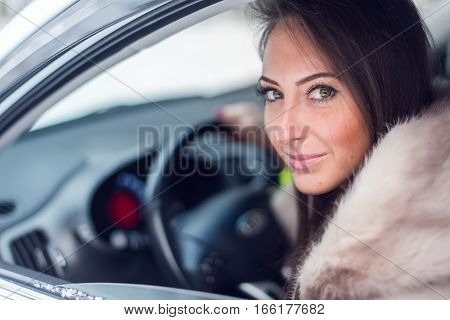 Smiling woman in fur coat sitting in car Winter picture