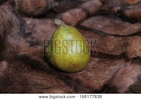 appetizing green sweet juicy oval shape pear lay on fur decor for table and home