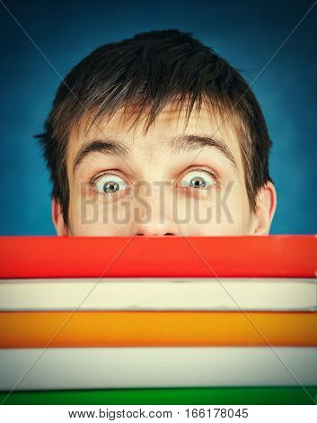 Toned Photo of Surprised Student behind the Books on the Blue Background
