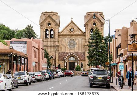 Santa Fe, USA - July 29, 2015: Downtown city street with parked cars and Cathedral Basilica of St. Francis of Assisi in New Mexico