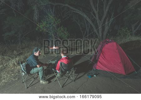 Adult couple relaxing in camping site by night. Adventure in National Park South Africa. Burning camp fire and tent in the background. Toned image.