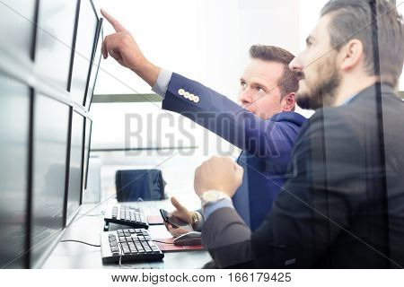 Businessmen trading stocks. Stock traders looking at graphs, indexes and numbers on multiple computer screens. Colleagues in discussion in traders office.
