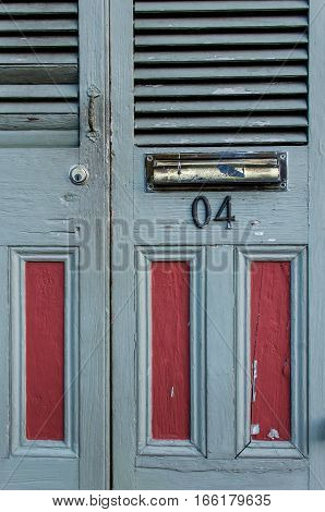 Slate grey and burgundy red door with number on it and mail slot closeup
