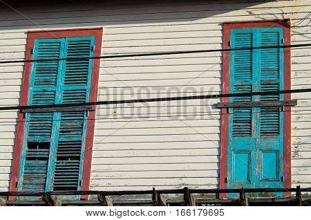 Old abandoned white wood panel house with turquoise blue doors with paint peeling off