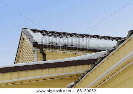 snow and icicles on the roof of an apartment house is sheathed with siding