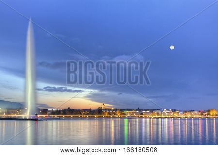 Geneva lake with famous fountain by night with full moon, Switzerland, HDR