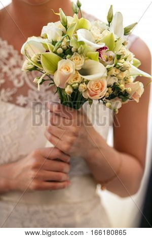 A Bouquet Of Calla And Roses Is Held By A Bride
